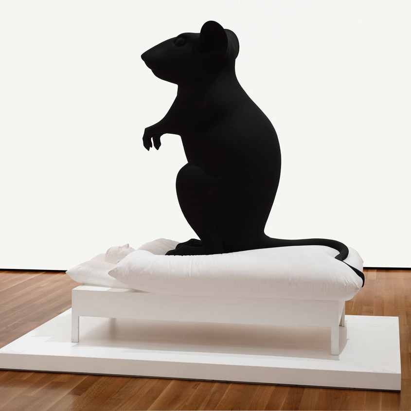 Image of a sculpture featuring a large black mouse sitting upright on top of a human tucked into bed
