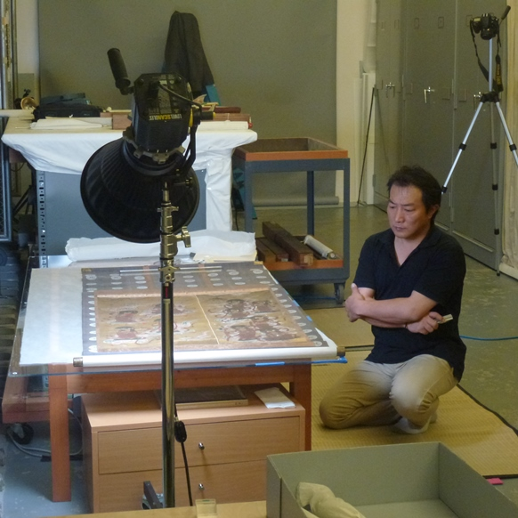 Conservator Tomokatsu Kawazu examines a painting on the light table for the Mellon Survey