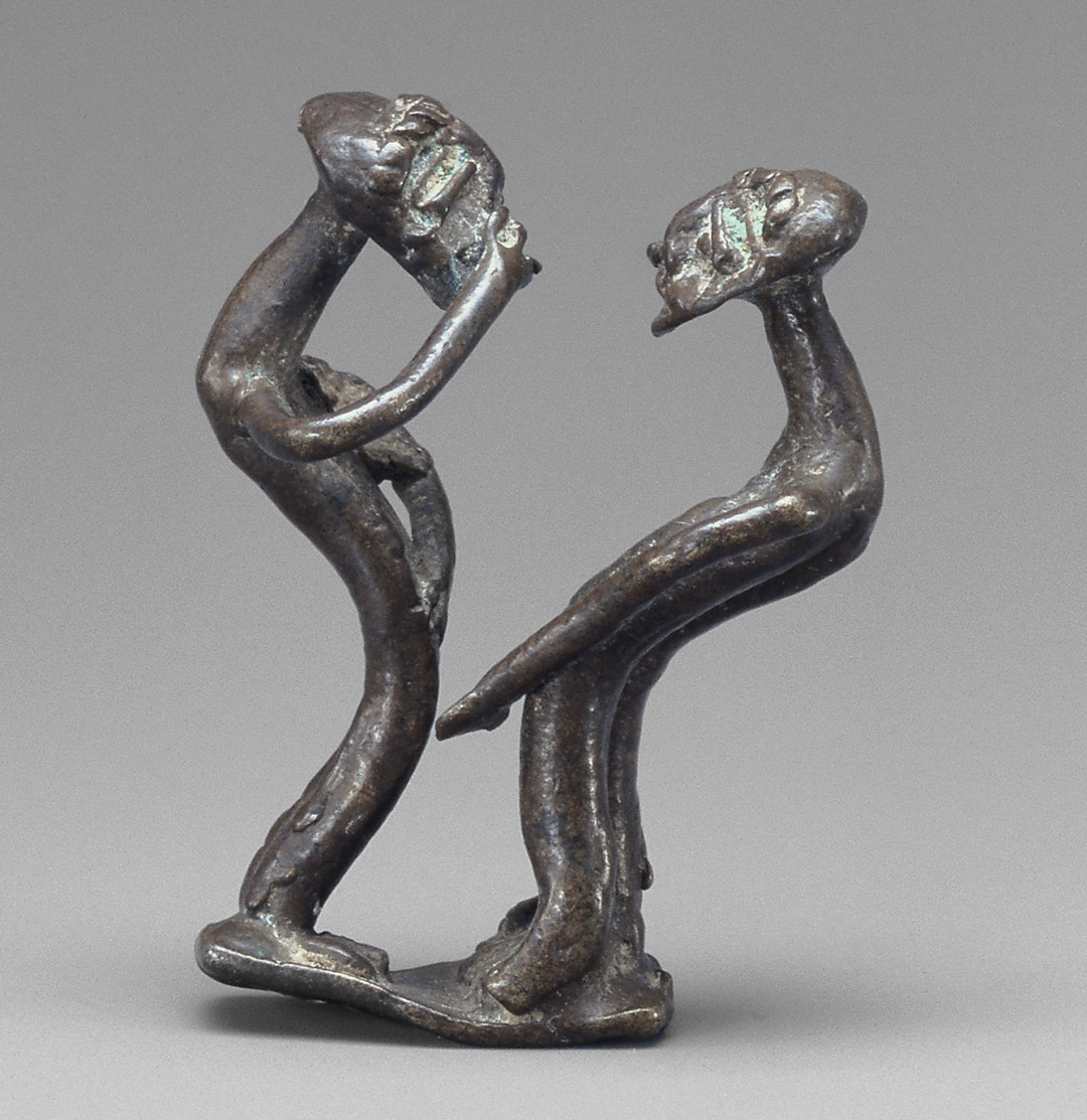 Copper sculpture of two figures facing each other