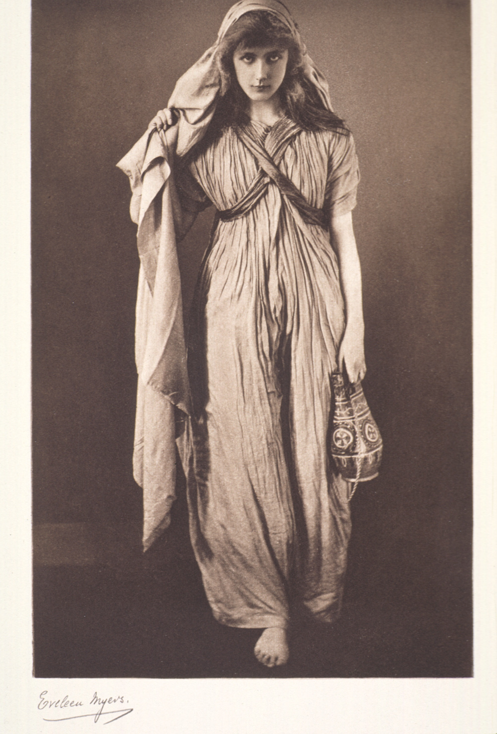 Black and white full-body portrait of a woman standing in long, white hooded robe looking at the viewer. She is carrying a water jug in her left hand