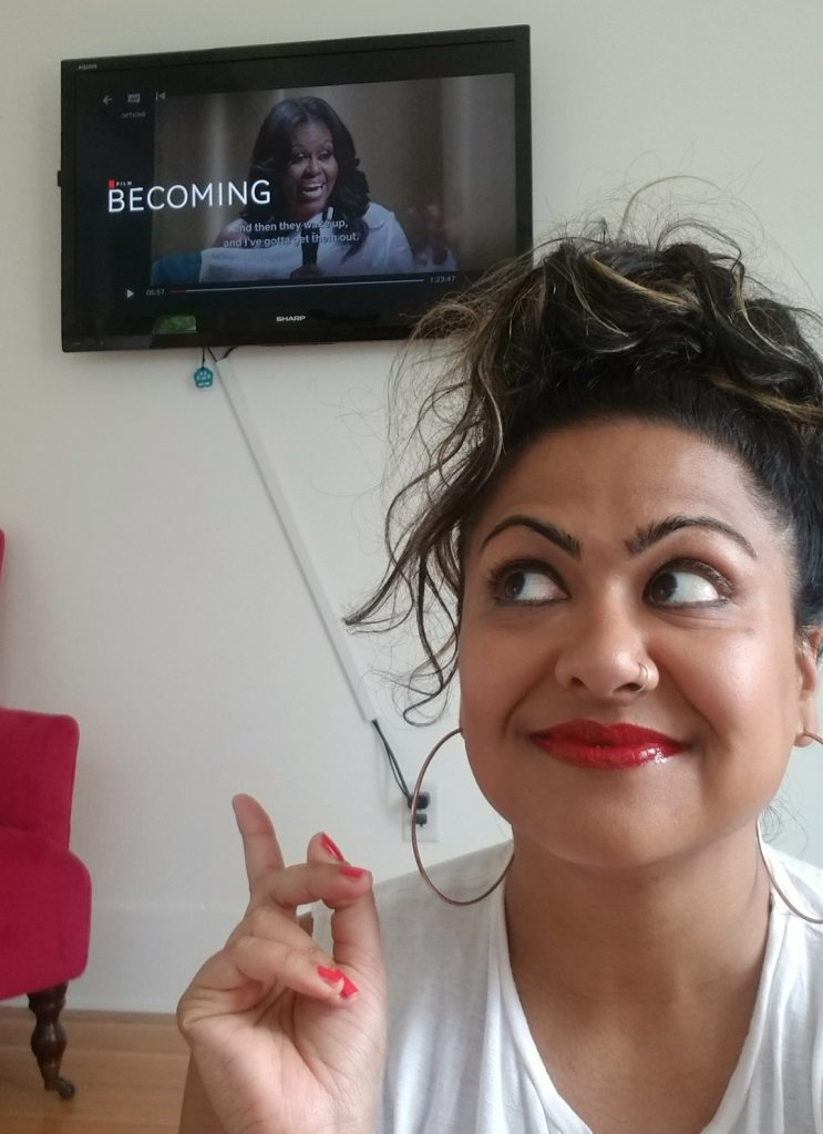 Priya Frank points at the TV featuring Becoming with Michelle Obama