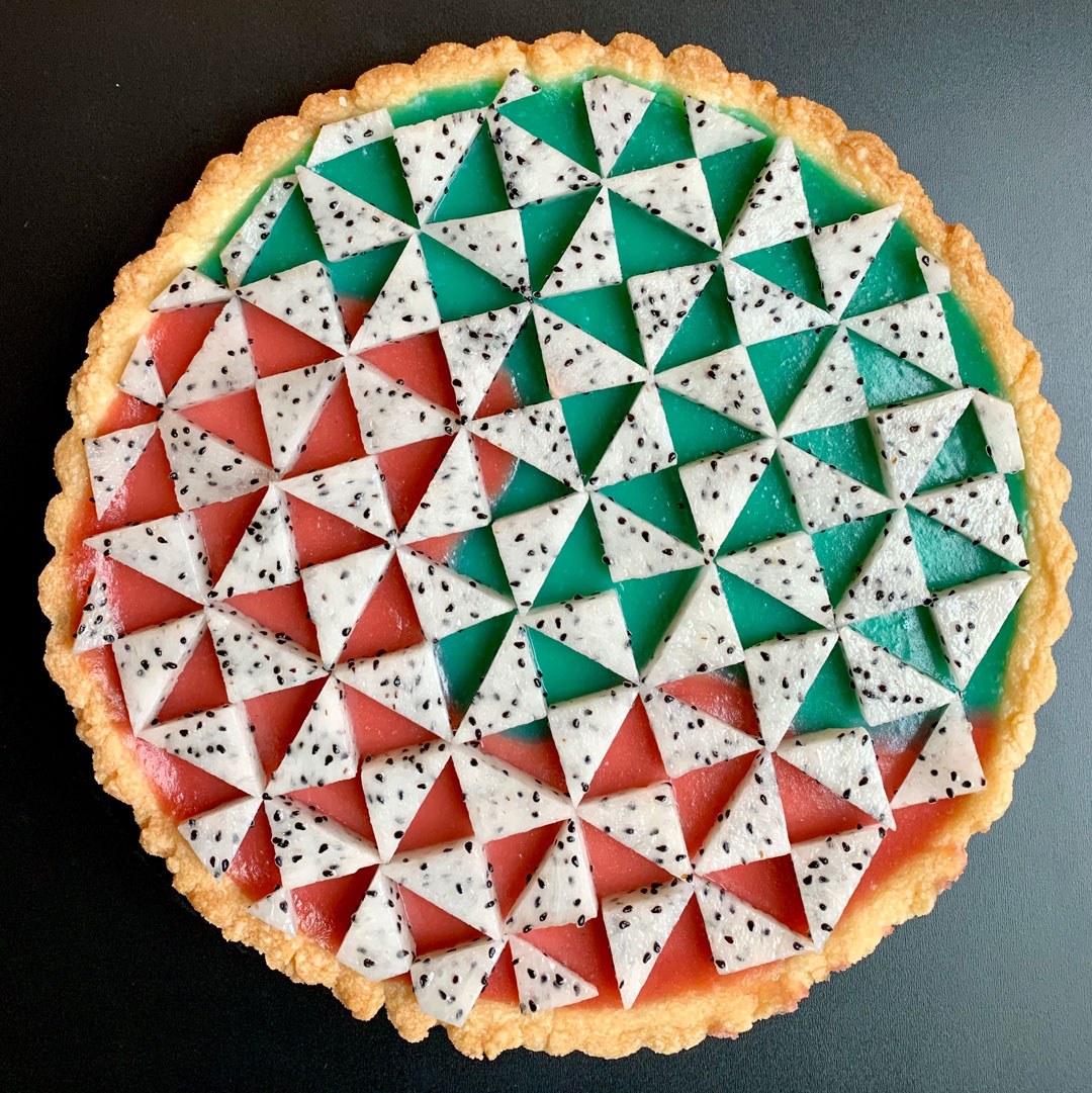 A colorful tart dessert covered in a fruit triangle design.