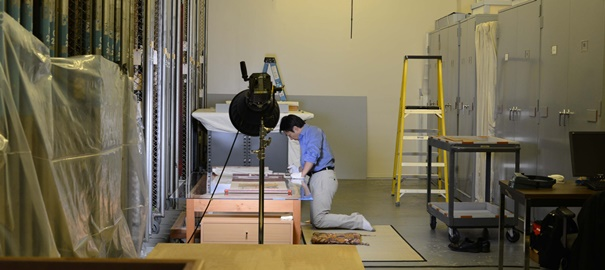 Mr. Kawazu surveying - Conservator Tomokatsu Kawazu studies Japanese paintings at SAM for the Mellon conservation survey