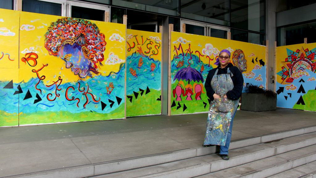Photo of Kimisha Turner standing in front of her large, colorful mural at SAM's entrance