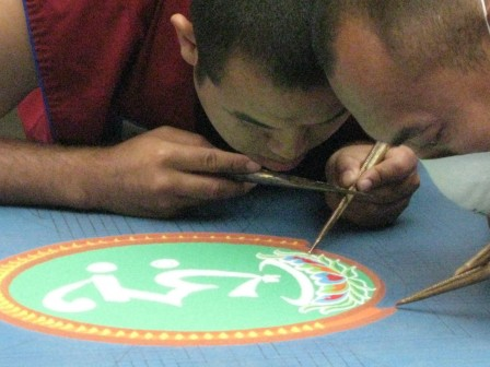 Gaden Shartse monks using chakpurs and colored sands to make a mandala at Seattle Asian Art Museum in collaboration with Dechenling
