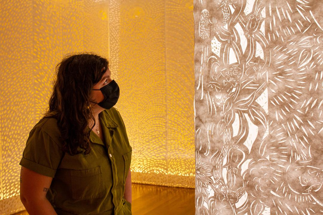 Image of a person wearing a mask looking at a lit paper sculpture installation by Barbara Earl Thomas